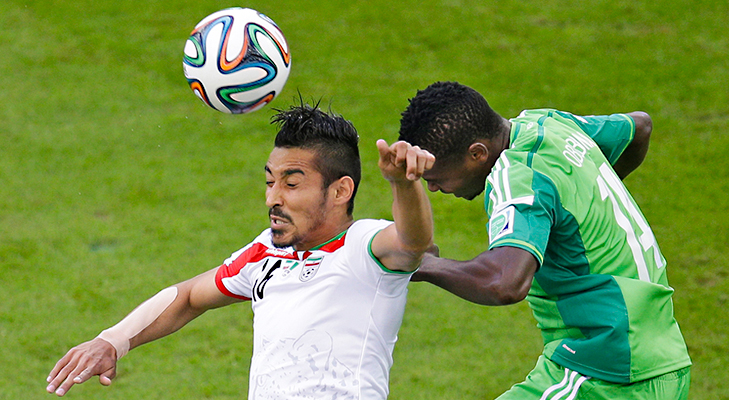 Iran's Reza Ghoochannejhad, left, and Nigeria's Godfrey Oboabona go for a header during the group F World Cup soccer match between Iran and Nigeria at the Arena da Baixada in Curitiba. @TheRoyaleIndia